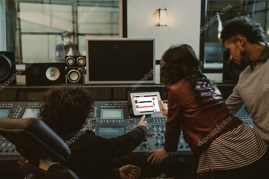 sound producers using tablet together at recording studio with soundcloud website on screen
