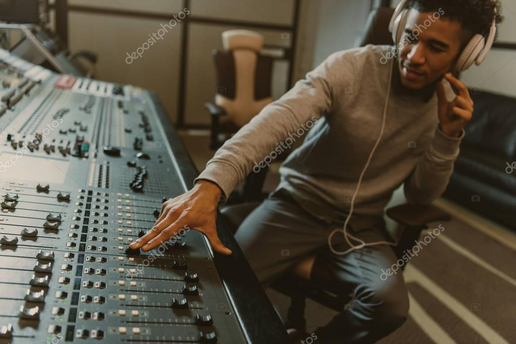 Young handsome sound producer working with analog equalizer at studio stock vector