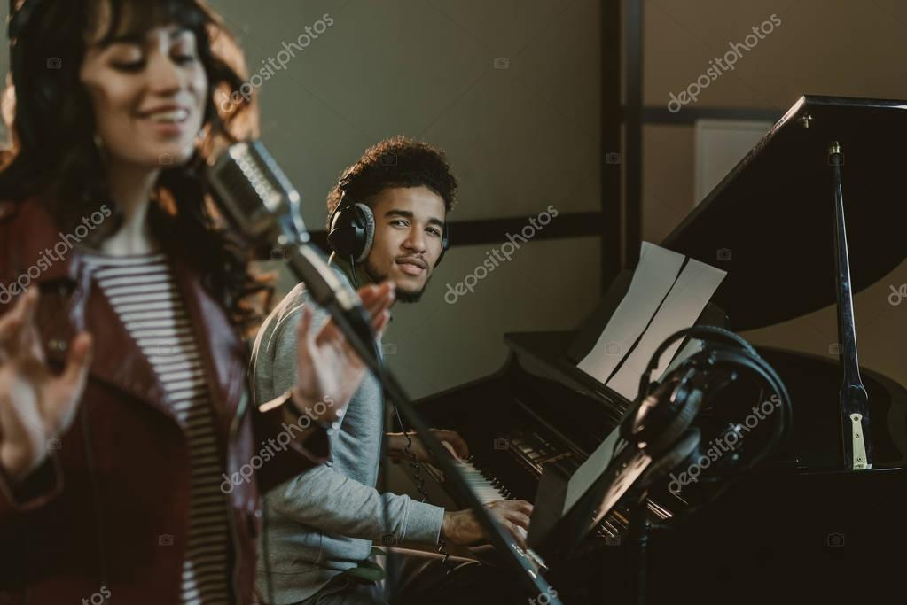 young handsome piano player looking at singer performing song