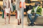 uomo afroamericano alla moda guardando le ragazze alla moda che cammina con i sacchetti di shopping nel centro commerciale