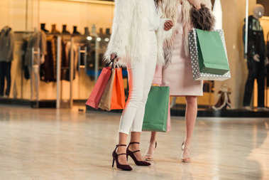 low section of fashionable multiethnic women in fur coats holding paper bags and shopping together in mall