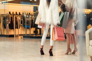 cropped shot of girls in fur coats holding paper bags while shopping together in mall