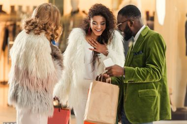 smiling fashionable multiethnic people looking into shopping bags in mall