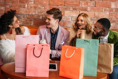 smiling fashionable multiethnic young people with shopping bags drinking coffee
