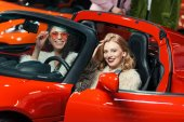 Photo fashionable smiling multiethnic women sitting in luxury red car and looking at camera