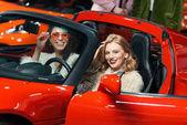 modisch lächelnde multiethnische Frauen, die im roten Luxusauto sitzen und in die Kamera schauen