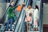 Stylový mladých mužů a žen nakupující na eskalátory v obchoďáku