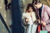 mladé stylové pár hledá do nákupní tašky v obchoďáku