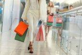 Oříznout záběr stylové ženy s papírové sáčky chůze nákupní centrum