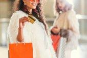 Fényképek fiatal nő vele bevásárló haver a gazdaság arany hitelkártya bundában
