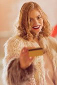 Fényképek gyönyörű fiatal nő, a bunda, arany hitelkártya a vásárlás