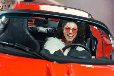 happy stylish young african american woman in fur coat driving luxury luxury car