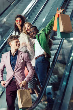 happy young multiethnic shoppers on escalator at mall with packages