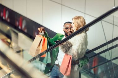 happy young interracial couple talking while riding escalator at shopping mall