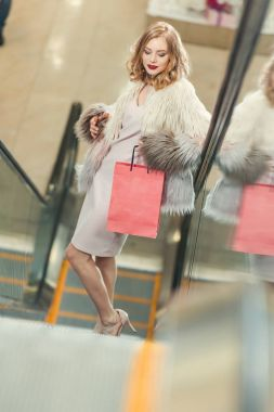 stylish woman with shopping bag riding escalator at mall
