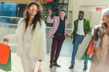 stylish women with shopping bags walking away from shocked boyfriends with empty pockets