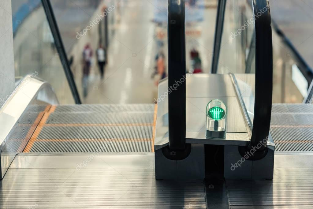 close-up shot of green light of escalator at shopping mall
