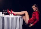 Fotografie sexy žena v červených šatech sedí u stolu v restauraci