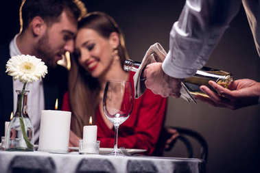 waiter pouring wine while beautiful couple having romantic date in restaurant on valentines day