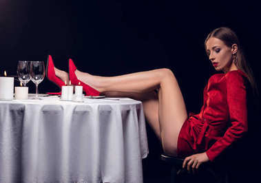 sexy woman in red dress sitting at table in restaurant