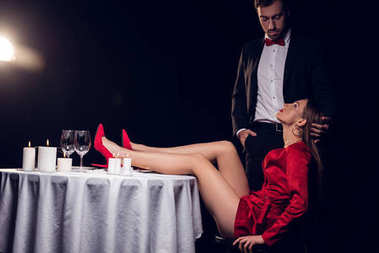 sexy woman in red dress sitting at table with her boyfriend