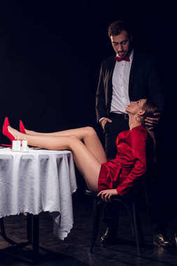 beautiful sexy woman in red dress sitting at table with her boyfriend