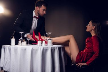 seductive woman in red dress sitting at table with her boyfriend