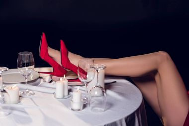 cropped view of sexy female legs in red hills at table in restaurant