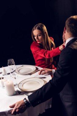 angry girlfriend slaping her boyfriend during romantic date in restaurant