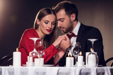 beautiful tender couple holding hands in restaurant