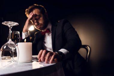 handsome upset man waiting for romantic date in restaurant