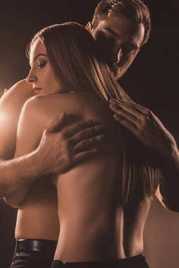 naked tender couple hugging, on brown with back light