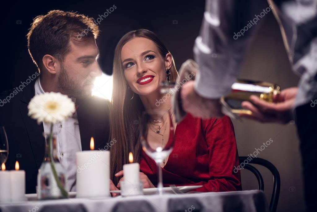 waiter pouring wine while happy couple having romantic date in restaurant on valentines day