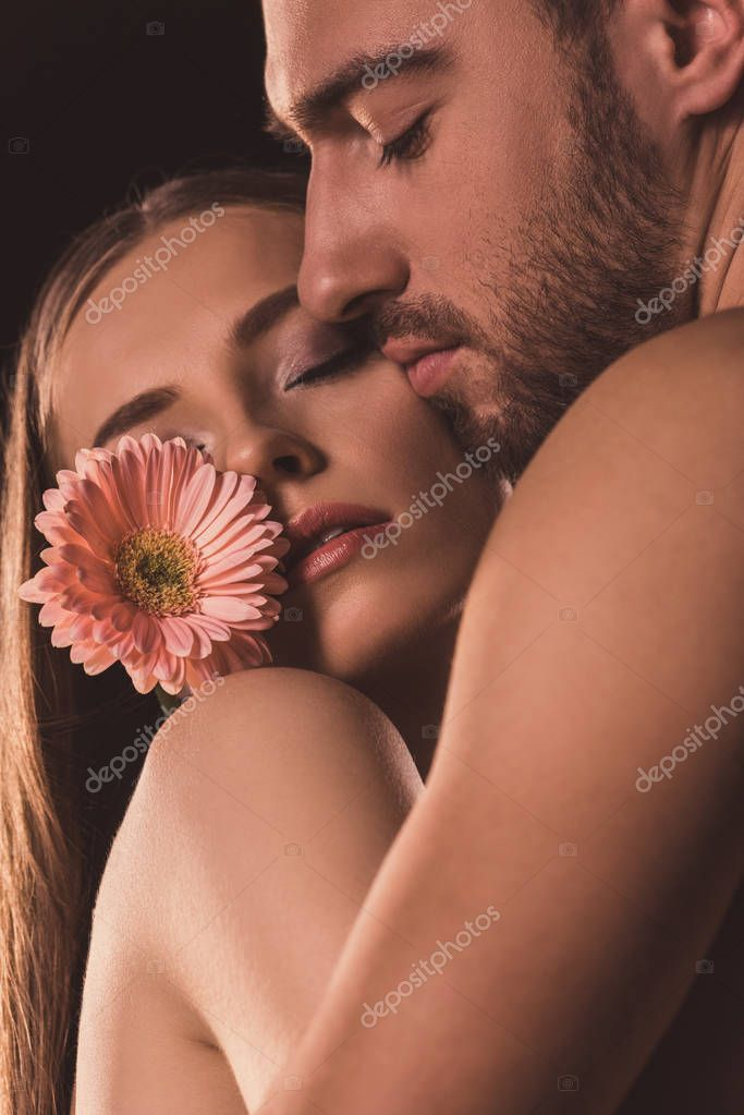 tender lovers hugging and holding gerbera flower