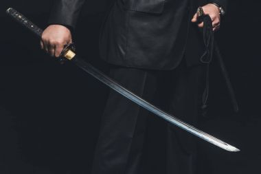 cropped shot of man with katana sword on black background