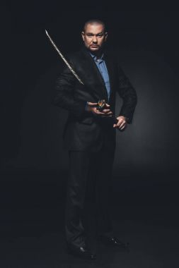 mature man in suit with japanese katana sword on black
