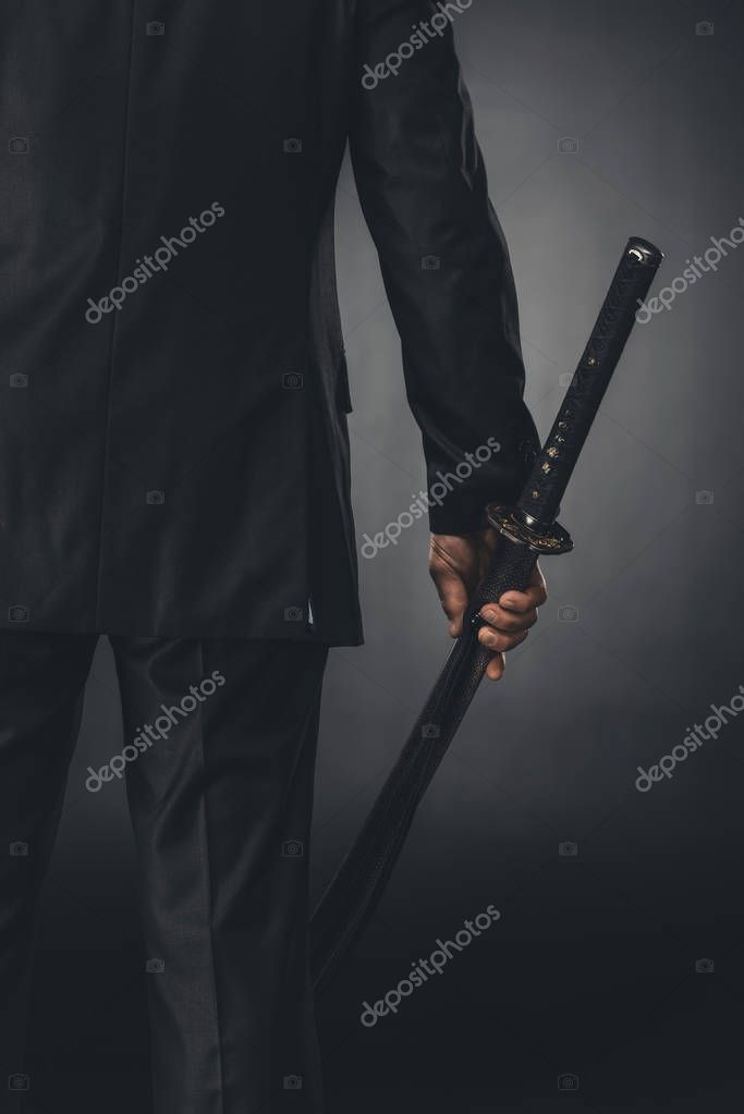 cropped shot of man in business suit with katana sword on black