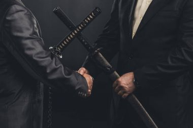 cropped shot of meeting of yakuza members in suits with katana swords isolated on black