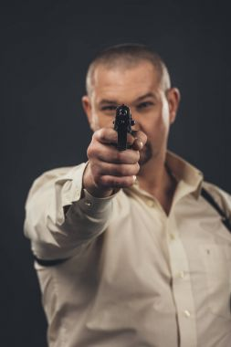 dangerous man aiming gun at camera isolated on black
