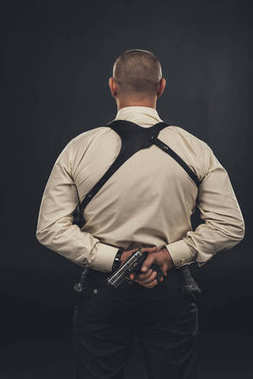 Back view of mafia member in shirt holding gun behind back stock vector
