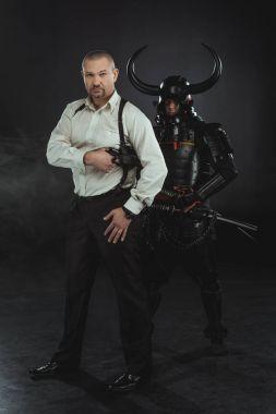 Man with gun and samurai behind him on black stock vector