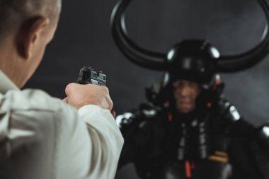 Close-up shot of man aiming on armored samurai with gun stock vector