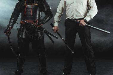 Cropped shot of modern man and samurai with katana swords on black stock vector