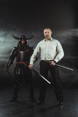 Modern man and samurai with katana swords on black stock vector
