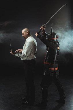 man using laptop while samurai making hit with sword