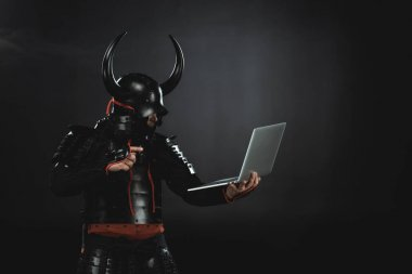 side view of armored samurai using laptop on black