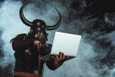 Armored samurai using laptop on dark background with smoke stock vector