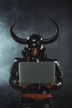 armored samurai warrior using laptop on dark background with smoke