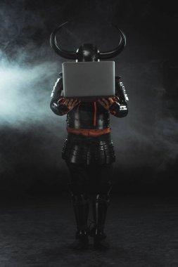 Armored samurai holding laptop on dark background with smoke stock vector