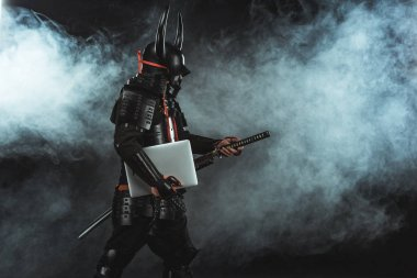 side view of samurai in traditional armor with laptop taking out sword on dark background with smoke